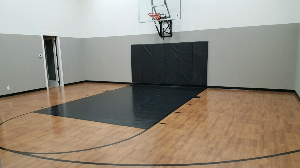 Millz House installed indoor basketball court in Eden Prairie featuring SnapSports Revolution Tuffshield athletic flooring in dark maple with black lane and black game lines and a 72 wall mount adjustable hoop