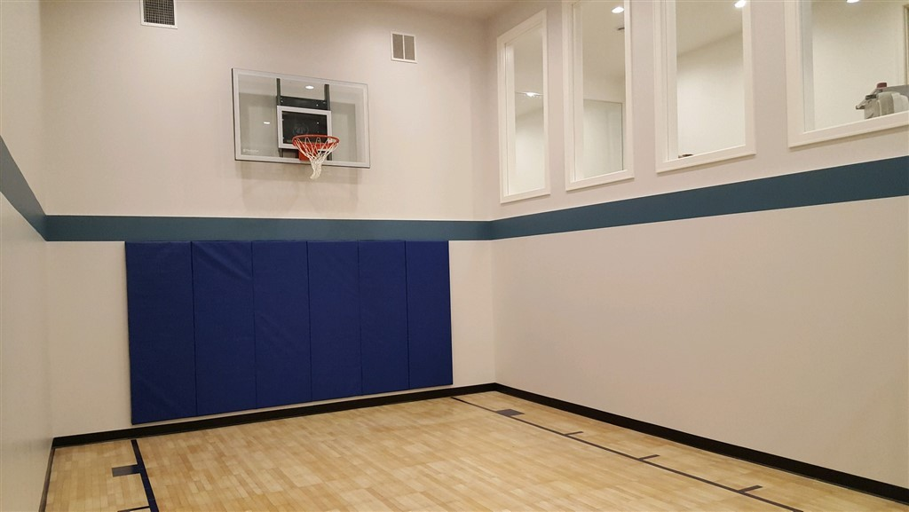 "Millz House indoor basketball court in Edina featuring SnapSports Maple Tuffshield with blue wall pads, blue court lines and 60"" Goalsetter baseline wall mount hoop"