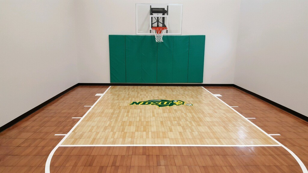 Customized indoor basketball court by Millz House in light and dark maple with custom NDSU logo