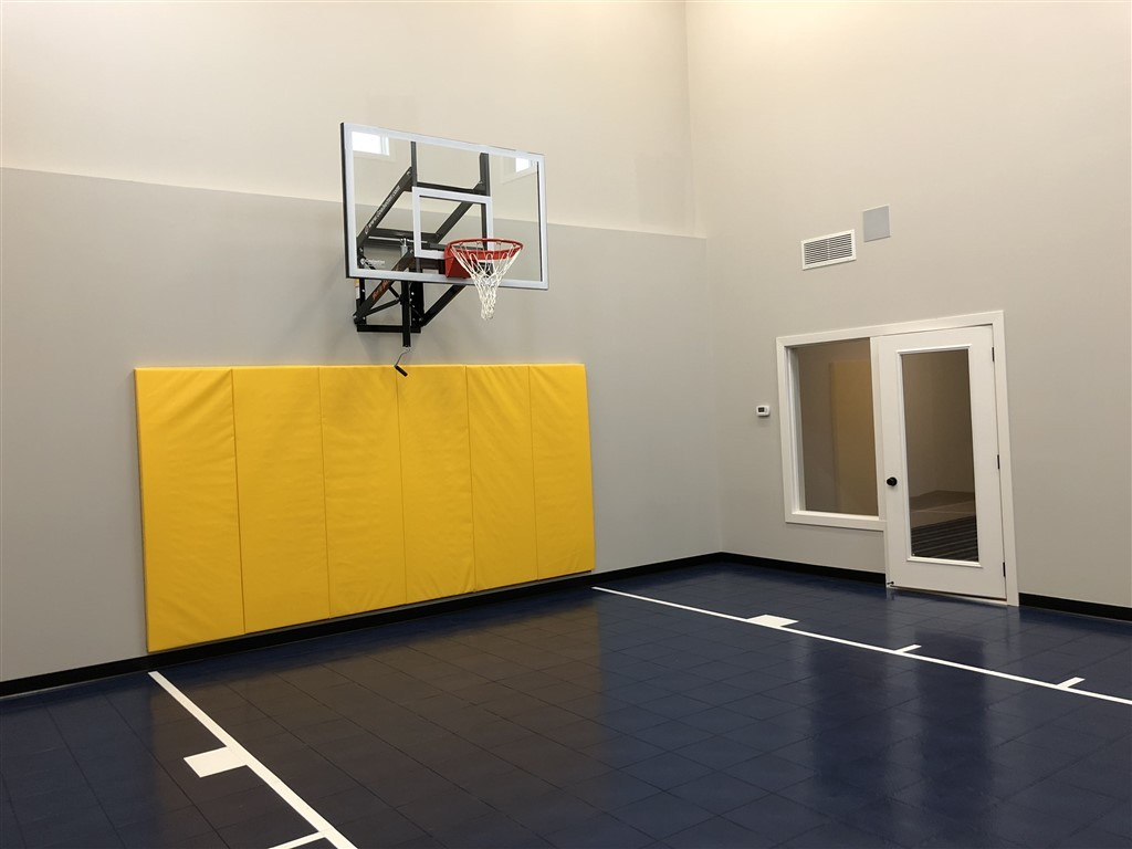 Twin Cities Spring Parade of Homes indoor basketball court featuring SnapSports athletic floor tiles installed by Millz House