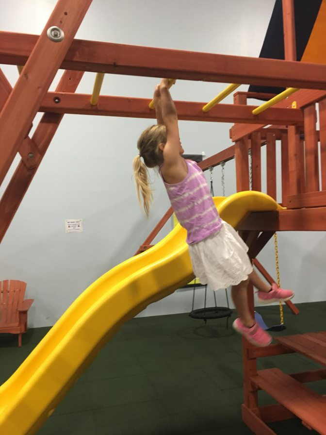 Child playing on monkey bars at Millz House Showroom in Apple Valley