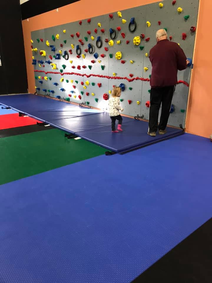 Child ready to climb on the climbing wall at Millz House Showroom in Apple Valley