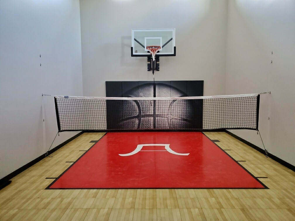 "Millz House helped this Plymouth family fully customize their game court! The court features SnapSports Light Maple Tuffshield athletic tiles with a Red Revolution Tuffshield lane, black game lines, 60"" Gladiator adjustable hoop, custom wall pad, and a multi-game net. The custom logo on the floor was hand-drawn by the family and recreated by the Millz House team for a meaningful one-of-a-kind design. No matter the sport, this family is ready for some indoor fun!!"