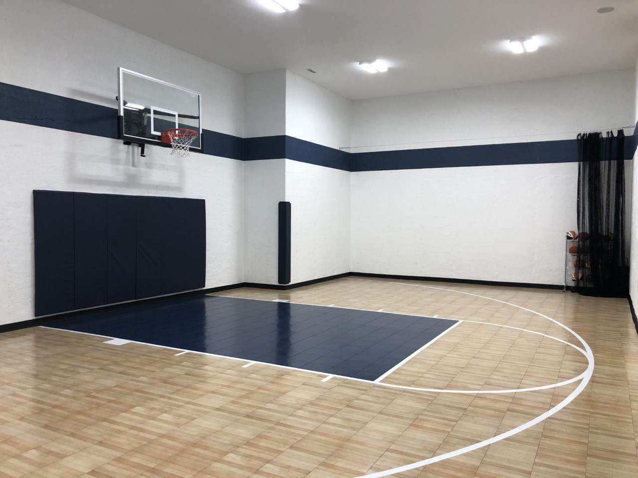 "1130 SF Game Court featuring SnapSports athletic tiles in Light Maple Tuffshield with a Navy Revolution Tuffshield lane, white basketball lines, 72"" Gladiator basketball hoop, nave wall and corner pads and black cove base"