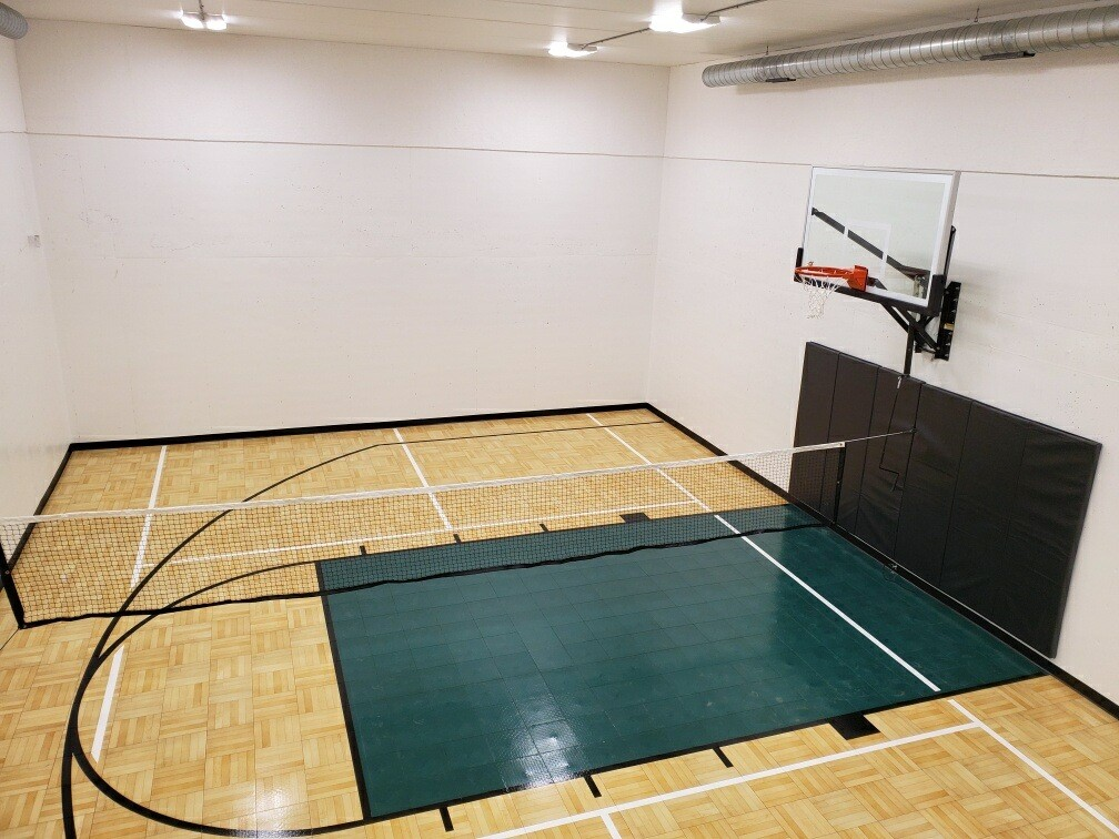 Indoor residential basketball court with maple parquet flooring and green basketball lane